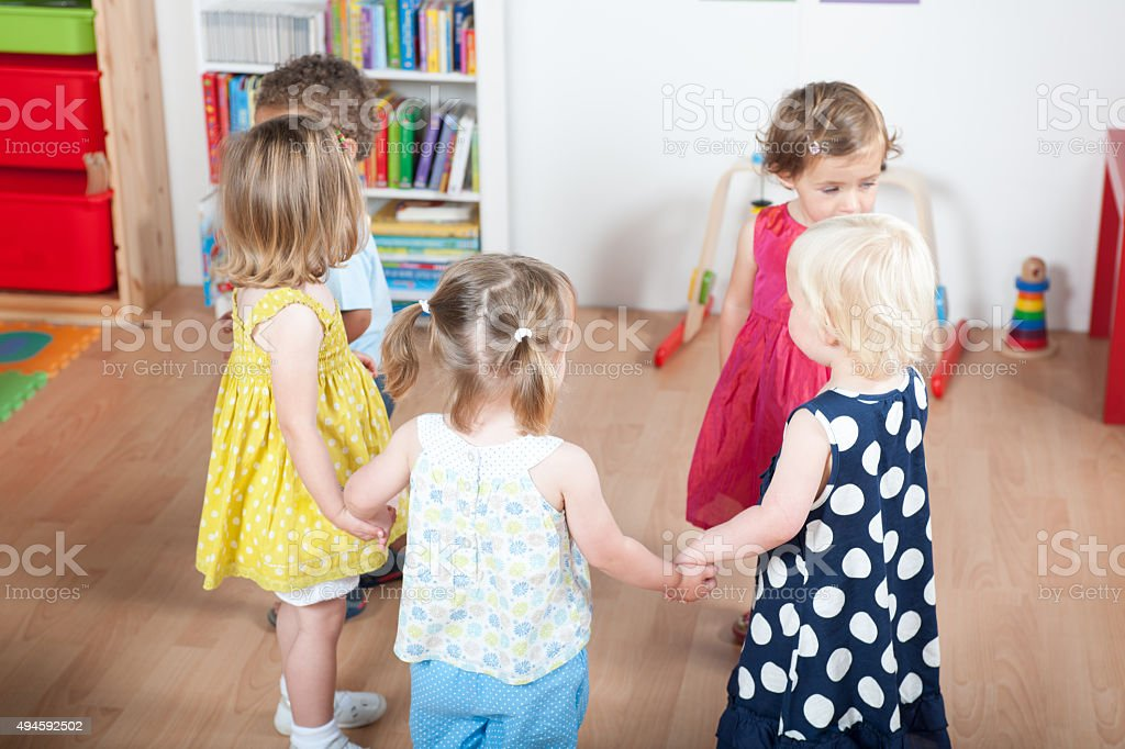 Group Of Happy Toddlers Holding Hands During Playtime stock photo