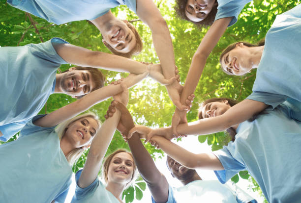 Group of happy volunteers collaborate at park Support concept. Happy volunteers holding hands in circle and smiling, teambuilding exercise, teamwork and help, view from below, copy space dedicated stock pictures, royalty-free photos & images