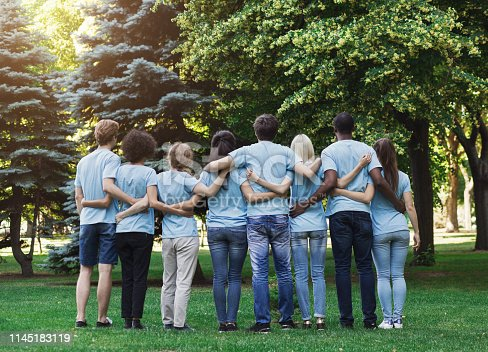 istock Group of happy volunteers embracing in park 1145183119