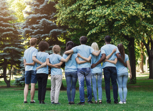 gruppe glücklicher freiwillige, die sich im park engagieren - wohltätigkeit und humanitäre hilfe stock-fotos und bilder
