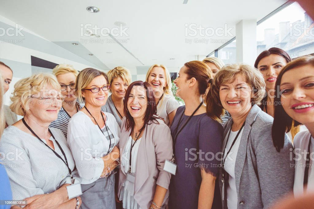Group of happy women attending a seminar Portrait of group of happy women attending a seminar. Mixed aged women standing together in a seminar hall. Active Seniors Stock Photo