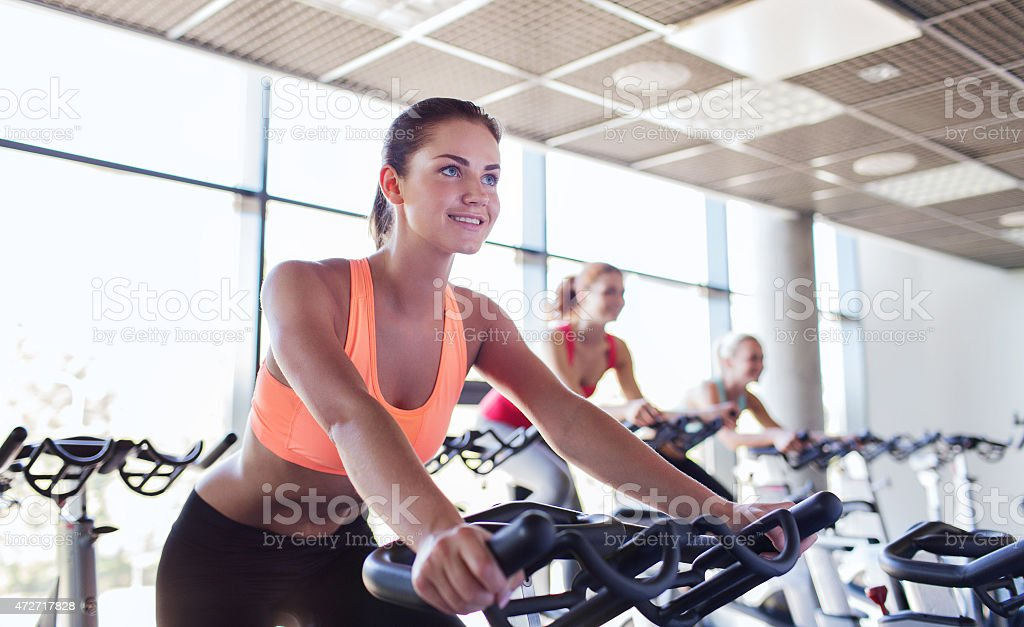 Group of happy women riding on exercise bikes in gym stock photo