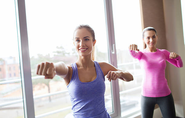 group of happy women working out in gym fitness, sport, training, gym and martial arts concept - group of happy women working out and fighting in gym self defense stock pictures, royalty-free photos & images
