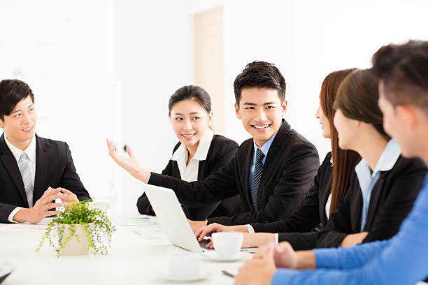 Group of happy young business people in  meeting stock photo