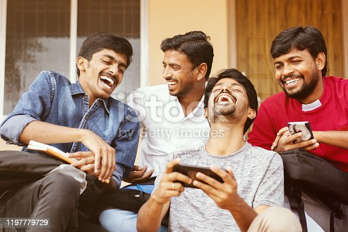644191686 istock photo Group of happy young college students by looking at mobile phone laughing loudly at university campus - Millennials enjoying online video content or social media by watching smart phone. 1197779729