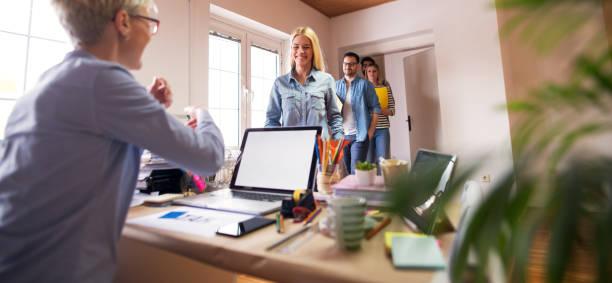 groep gelukkige jonge ingenieurs is ingelicht dat zij kreeg de baan als ze het kantoor van hun nieuwe baas betreden. - netherlands map stockfoto's en -beelden