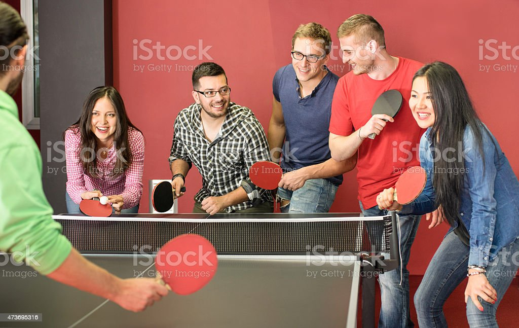 Group of happy young friends playing ping pong table tennis stock photo