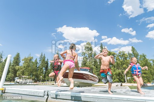 A mixed group of four young children run and jump off the dock at a lake. There are several boats in the background. What a glorious summer day!