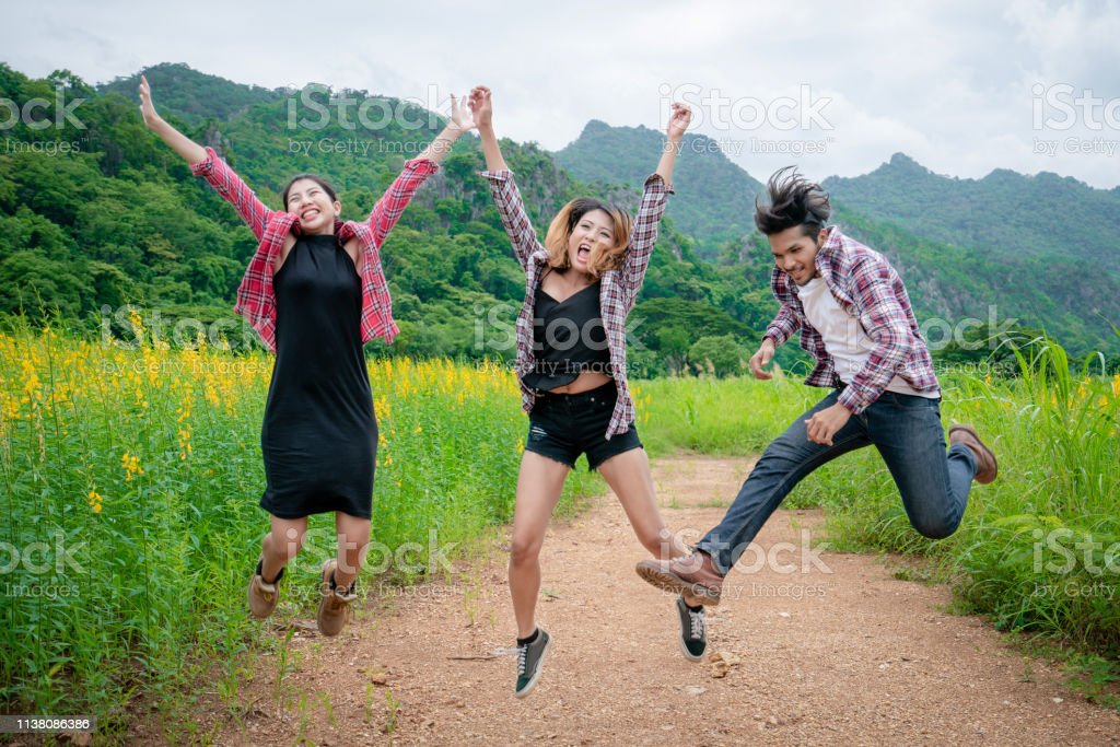Group of happy young people jumping in the air while traveling in...
