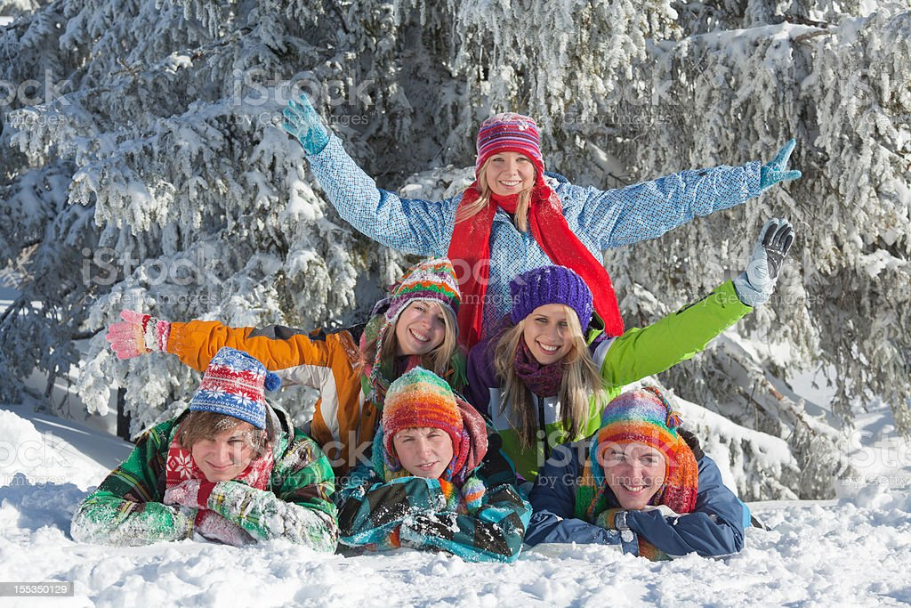Group of happy young people lying in snow royalty-free stock photo