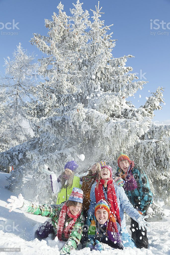 Group of happy young people lying in snow throwing snowballs royalty-free stock photo