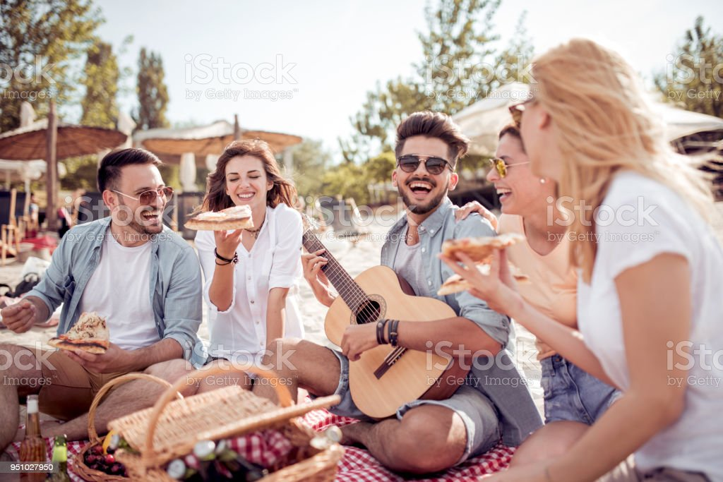 Group of happy young people sitting together on the beach stock photo