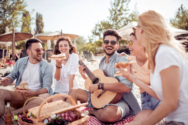 group of happy young people sitting together on the beach - vacations food stock pictures, royalty-free photos & images