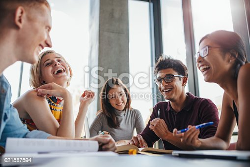 istock Group of happy young students in library 621587594