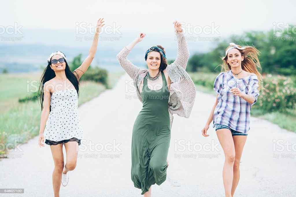Group of happy young women dancing on the road stock photo