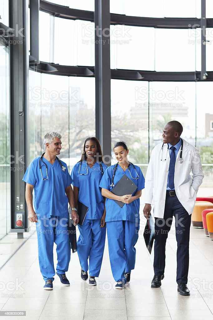 group of health care workers walking in hospital stock photo
