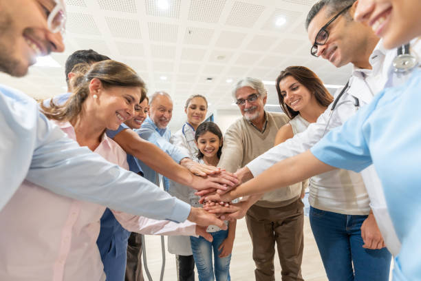 Group of healthcare workers and patients of different ages in a huddle all with hands in smiling Group of healthcare workers and patients of different ages in a huddle all with hands in smiling at the hospital community health stock pictures, royalty-free photos & images