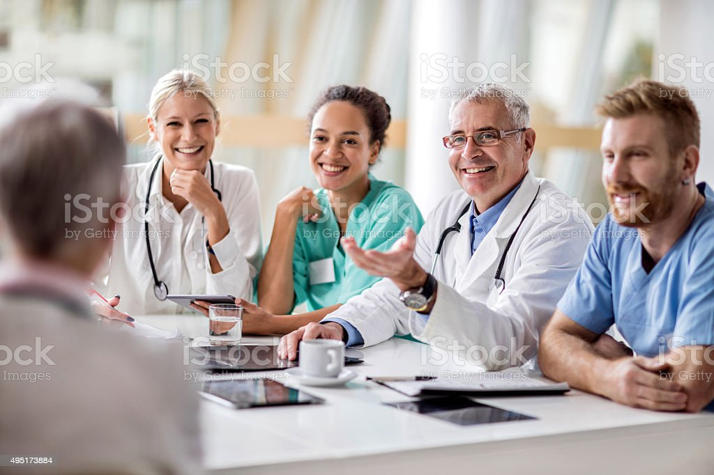 Group of healthcare workers sitting at the table and communicating. stock photo