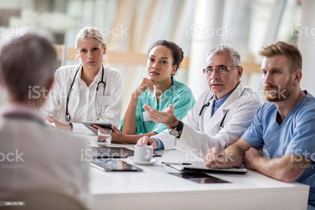 Group of healthcare workers talking on a meeting at hospital. stock photo