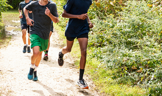 istock Group of high school boys running on a path 1155214343