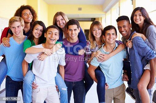 istock Group Of High School Students Giving Piggybacks In Corridor 499170823