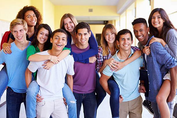 group of high school students giving piggybacks in corridor - 休閒活動 主題 個照片及圖片檔