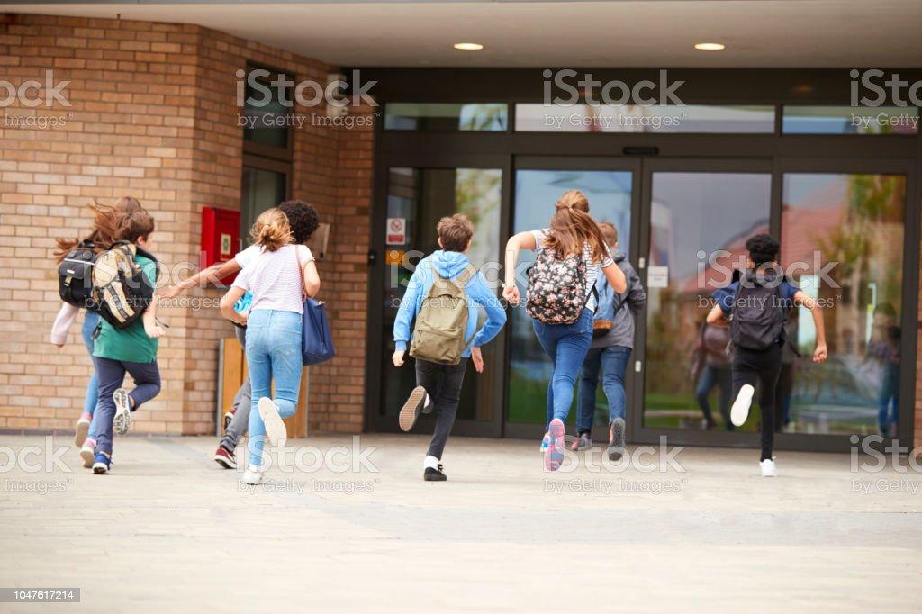 Grupo de estudiantes de secundaria en el edificio de la escuela al comienzo de clase - foto de stock