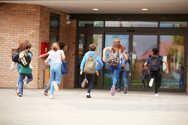 grupo de estudiantes de secundaria en el edificio de la escuela al comienzo de clase - regreso a clases fotografías e imágenes de stock