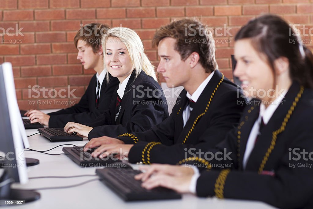group of high school students using computers stock photo