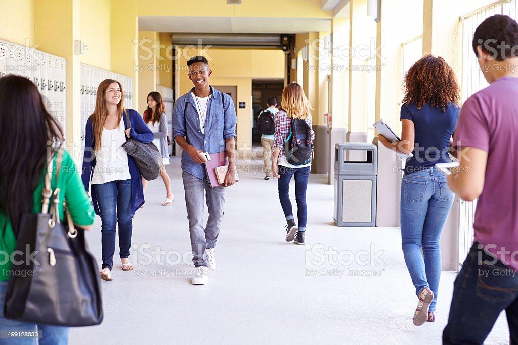 Group Of High School Students Walking Along Hallway stock photo