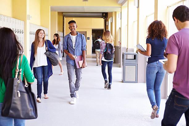 グループの高校生に沿って歩くの廊下 ストックフォト