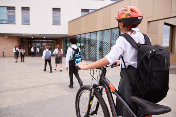 grupo de estudiantes de secundaria con uniforme al llegar a la escuela, caminar o montar en bici - regreso a clases fotografías e imágenes de stock