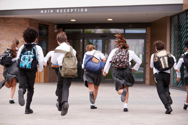 group of high school students wearing uniform running into school building at beginning of class - private school stock photos and pictures