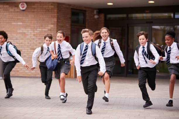 group of high school students wearing uniform running out of school buildings towards camera at the end of class - униформа стоковые фото и изображения