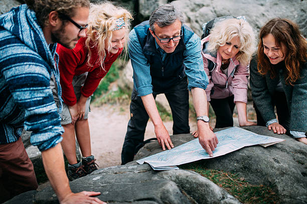 group of hikers checking route on map - guide stockfoto's en -beelden
