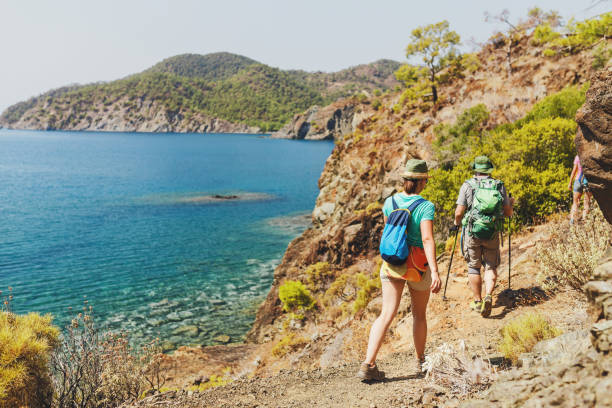 Group of Hikers walking by Lycian Way trail along wild beach and mountains in Turkey stock photo