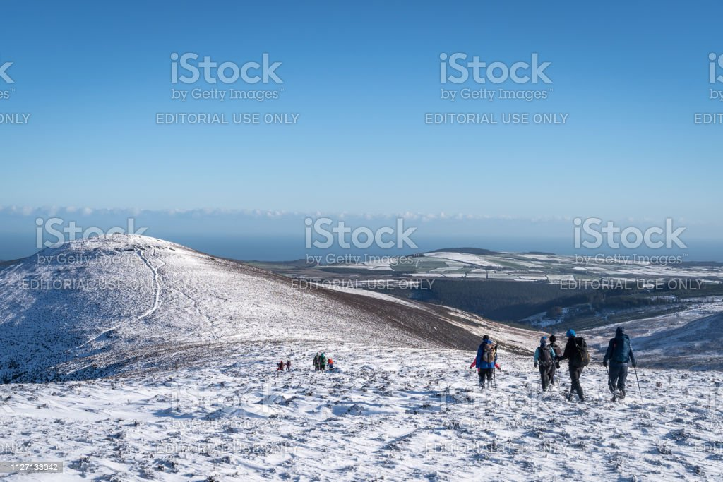 Group of hikers walking in the snow across a vast beautiful wild...
