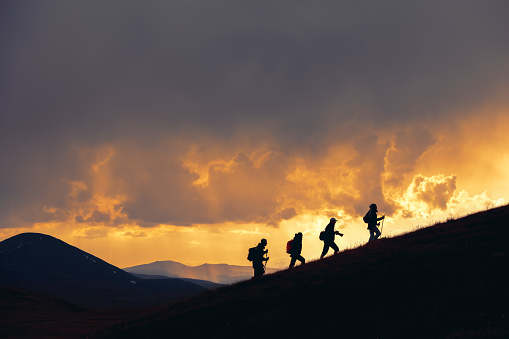 Group of unrecognizable hikers are walking at majestic sunset in mountains