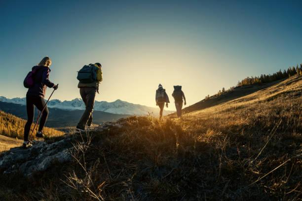 grupo de excursionistas camina en las montañas al atardecer - excursionismo fotografías e imágenes de stock
