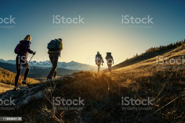 Photo of Group of hikers walks in mountains at sunset