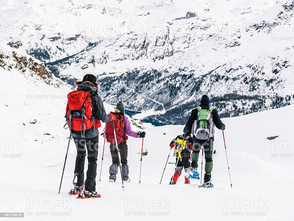 Group of hikers with snowshoes in the snowy mountains stock photo