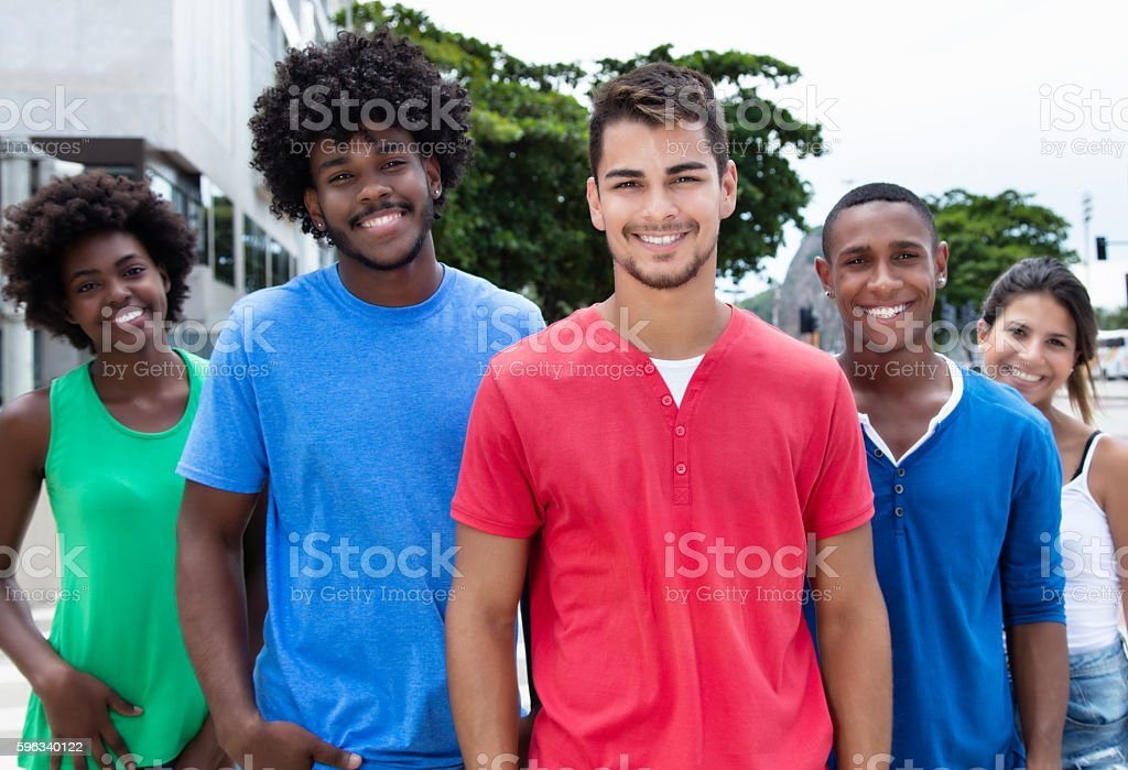 Group of hip young adults laughing at camera in city Lizenzfreies stock-foto