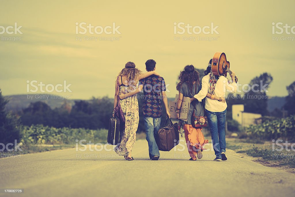 Group of hippie friends walk away stock photo