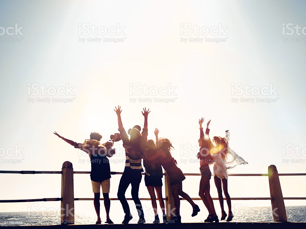 Group of hipster friends celebrating their vacations at the beach stock photo