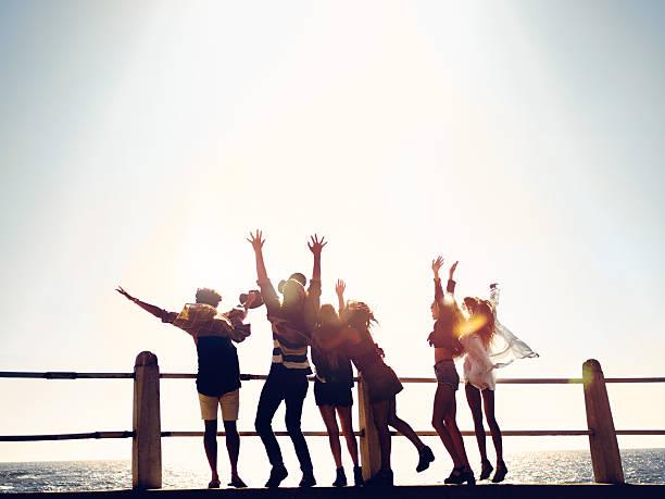 のグループヒップスターご友人とのお祝いに、バケーションビーチで ストックフォト