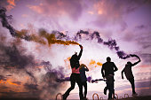 Group of hipster friends playing with smoke bombs at sunset