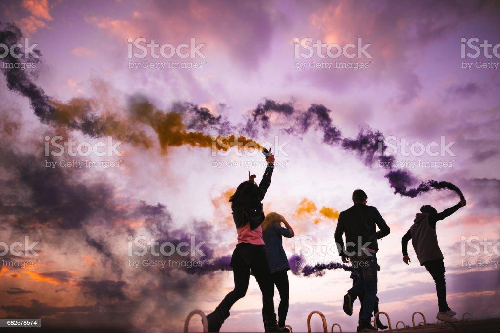 Grupo de amigos hipster jugando con bombas de humo al atardecer - foto de stock