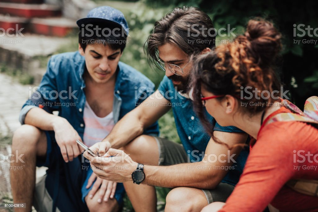 Group of hipster people are looking in the phone at the park stock photo