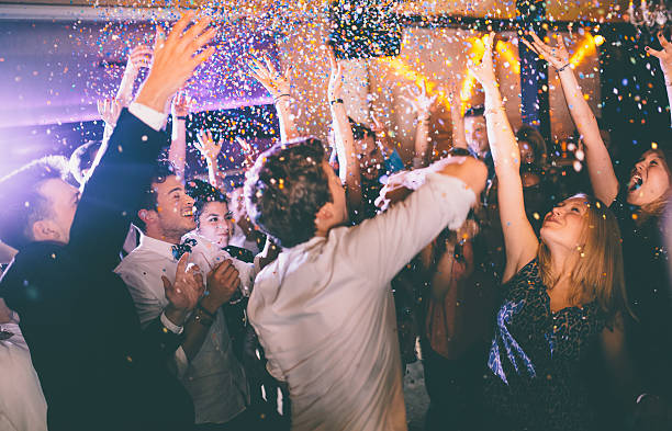 group of hipsters throwing confetti at a party in celebrations - dance floor stock photos and pictures