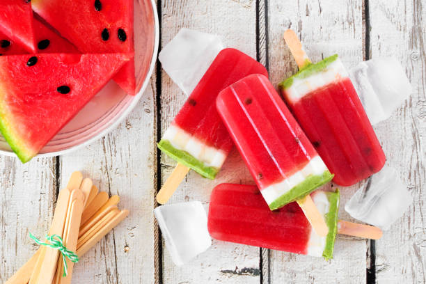 Group of homemade summer watermelon popsicles, top view over rustic white wood stock photo